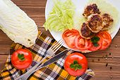 Fried Meat Patties, Tomatoes And Peking Cabbage On A Wooden Table. Top View poster
