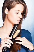 young woman use hair straightener iron, studio shot