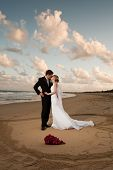 Bride And Groom Kissing Inside A Love Heart In The Sand