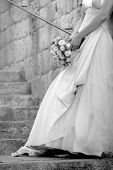 foto of bridal shower  - Black and white photo of a bride leaning against a wall holding her bouquet - JPG