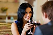 foto of restaurant  - Young happy couple romantic date drink glass of red wine at restaurant, celebrating valentine day