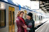 Freunde, die einander auf dem Bahnhof Gruß