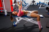 Beautiful girl in sports to a hall carries out exercise with a bar in the gym Bar Bench Press