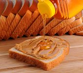 Closeup of making a peanut butter and honey sandwich. Slice of bread with PB  already spread and honey being poured on. Shallow Depth of field with slices of bread in the background.