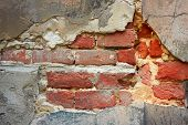 pic of fragmentation  - Fragment of old brick wall on a foundation with destroyed stucco close - JPG