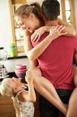 Romantic Couple Hugging In Kitchen Being Interrupted By Daughter