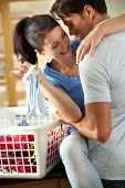 Romantic Couple Sorting Laundry In Kitchen