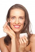 Portrait of beautiful healthy caucasian woman applying moisturizing cream on her face. Middle Aged
