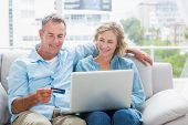 pic of couch  - Smiling couple sitting on their couch using the laptop to buy online at home in the sitting room - JPG