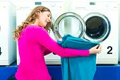 Woman in a launderette, washing her dirty laundry, in the background are washing machines, a female