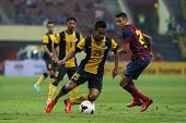 KUALA LUMPUR - AUGUST 10: Malaysia's Wan Zack Haikal (25) takes on Barcelona's Cristian Tello (20) in a game at the Shah Alam Stadium on August 10, 2013 in Malaysia. Barcelona wins 3-1.