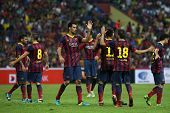 KUALA LUMPUR - AUGUST 10: FC Barcelona's players (maroon/blue) celebrate a goal scored against Malaysia at the Shah Alam Stadium on August 10, 2013 in Malaysia. FC Barcelona wins 3-1.