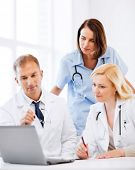 healthcare, medical and technology - group of doctors looking at laptop on meeting