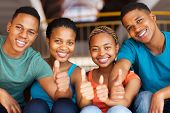 group of cheerful students wit thumbs up