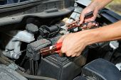 stock photo of dead-line  - Car mechanic uses battery jumper cables to charge dead battery - JPG