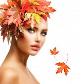 Autumn Woman Fashion Portrait. Beauty Autumn Girl with colorful yellow and red Leaves on her Head. H