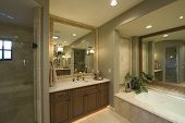 View of a modern bathroom with bathtub and square mirror at washbasin in home