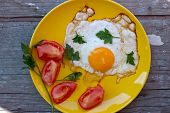 Scrambled eggs with tomato in a yellow plate