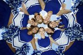 stock photo of huddle  - Directly below shot of happy cheerleaders forming huddle against sky - JPG