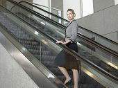 Full length of confident businesswoman standing on escalator