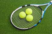 Tennis Racket With Three Balls Lies On A Green Lawn Surface. Tennis Concept