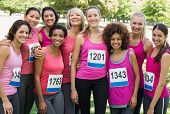 Group of happy women participating in breast cancer marathon standing together park