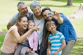 Man taking picture of his cheerful extended family at the park