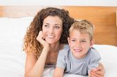 Happy mother and son lying on bed looking away at home in bedroom
