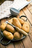 wooden peeler and potatoes on wooden table