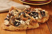 stock photo of sauteed  - Naan bread topped with black olives sauteed mushrooms feta cheese and hummus - JPG