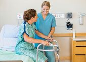 Happy mid adult nurse assisting female patient using walking frame in hospital