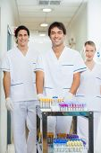 Portrait of confident lab technicians with medical cart in hospital corridor