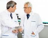 Male researchers shaking hands in hospital