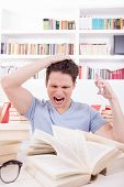 Upset Student With Hand On His Head Surrounded By Books