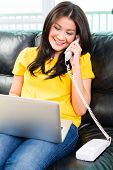 Young Asian handsome woman sitting on couch multitasking by using laptop and telephoning with phone
