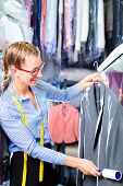 pic of lint  - Female cleaner in laundry shop checking clean clothes removing lint with roller - JPG