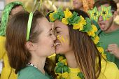 Cheerful couple of Brazilian girlfriends soccer or sports fans almost kissing each other celebrating