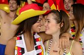 Cheerful couple of German lesbian soccer fans almost kissing celebrating victory.