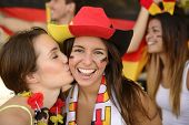 German couple of soccer sport fans kiss celebrating victory.