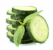 Sliced fresh cucumber with basil, isolated on white