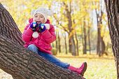 Little girl with binocular sits on inclined tree trunk in autumn park