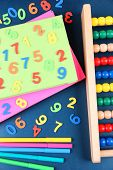 Colorful numbers, abacus, books and markers on school desk background