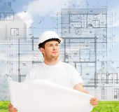 building, developing, construction and architecture concept - male architect in helmet looking at bl