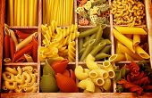 stock photo of pasta  - Various Raw Dry Colorful Pasta with Pasta Shells and Fusillini closeup in Wooden Sections - JPG