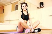 Young smiling fit woman sitting on yoga mat at gym