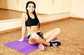 Young smiling fit woman sitting on the floor at gym