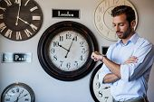 Handsome businessman checking the time at the local bar beside wall of international clocks