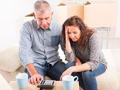 Mature couple at new home sitting and using calculator to sum their expenses and loans