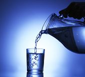 Pour water from  pitcher into  glass, on dark blue background