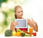 fitness, diet, technology, health and food concept - sporty woman with fruits and vegetables pointing at tablet pc
